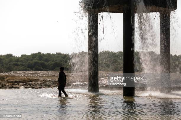 A boy stands as water falls from a water pipe leakage in Karachi Pakistan on Monday Dec 24 2018 Women and children walk miles each day in search...
