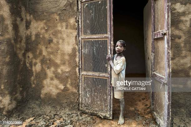 A boy stands at a door during the annual rendering of the Great Mosque of Djenne in central Mali on April 28 2019 Several thousand residents of the...