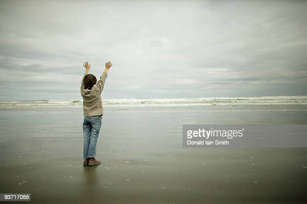 boy stands at beach with arms outstretched - palmerston north new zealand stock pictures, royalty-free photos & images