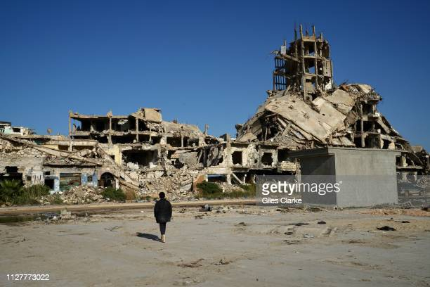Boy stands before ruins in Benghazi's old city on February 4, 2019 in Libya. After the Libyan revolution in 2011 and the downfall of the Gaddafi...