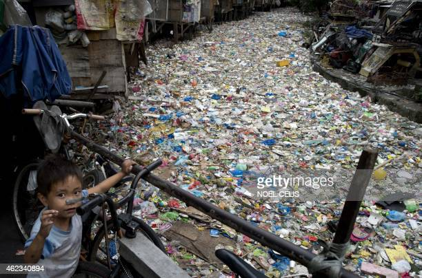 A boy stands beside a river filled with garbage in Manila on January 27 2015 AFP PHOTO / NOEL CELIS