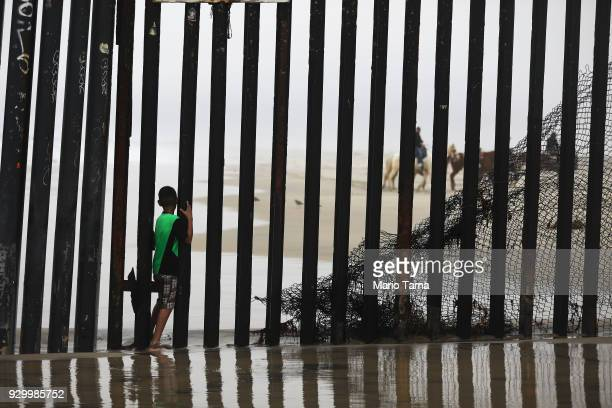 A boy stands between posts in the USMexico border fence as people on the American side ride horses in the distance in Tijuana's beach district on...