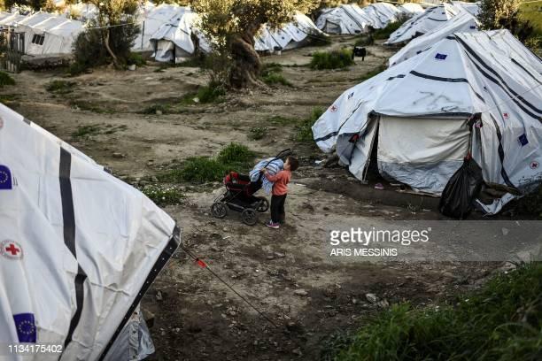 Boy stands between tents at an unofficial camp outside the refugee camp of Moria on the Greek island of Lesbos, on March 19, 2019. - When thousands...