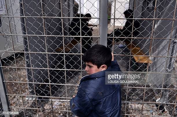 Boy stands by a gate at the Greek Macedonian borders, near the village of Idomeni on March 8 where thousands of refugees and migrants are stranded....