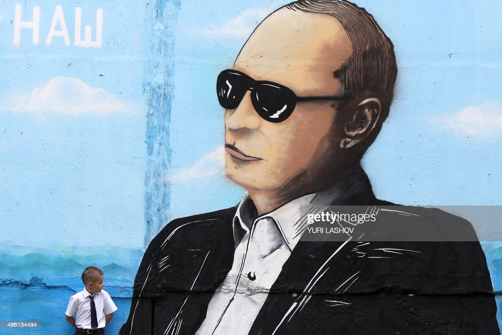 A boy stands by a wall sprayed with a graffiti depicting Russia's President Vladimir Putin in the Crimean city of Simferopol on September 1, 2015. / AFP / YURI