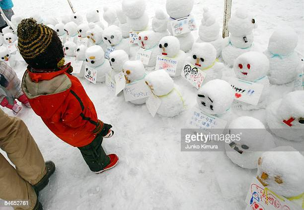 A boy stands by snowmen during the 60th Sapporo Snow Festival on February 5 2009 in Sapporo Japan The 60th Sapporo Snow Festival takes place from...