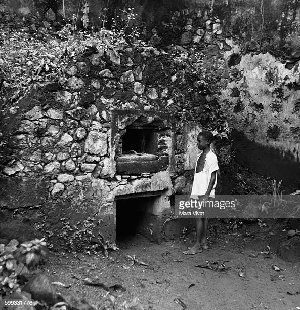 A boy stands by the cell where a murderer survived the pyroclastic flow from Mount Pelee which killed all the other 40000 inhabitants of St Pierre in...