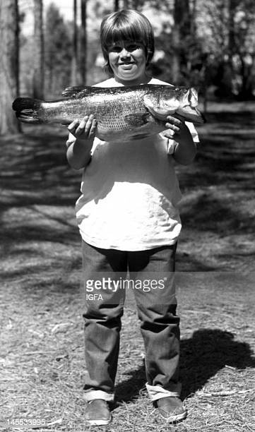 A boy stands holding an 8 pound 6 ounce largemouth bass he caught on 10 pound line on March 19 1972 in Florida