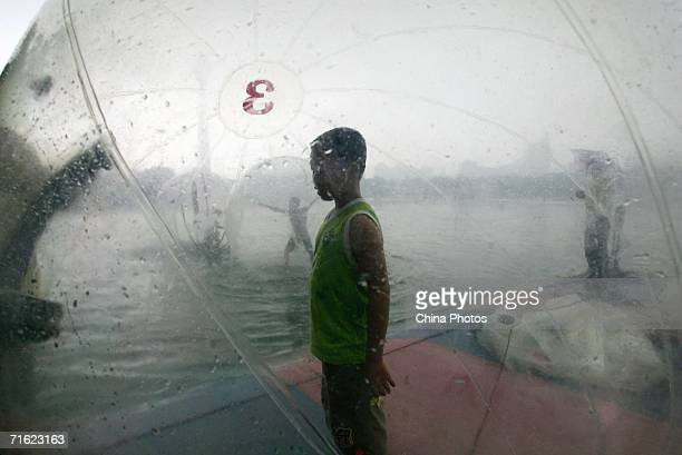 A boy stands in a water walking ball at Yuyuantan Park on August 10 2006 in Beijing China The ball that is 25 meters in diameter and filled with...