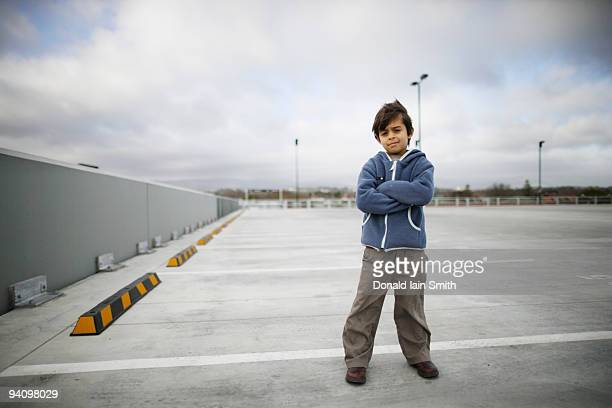 Boy stands in car park