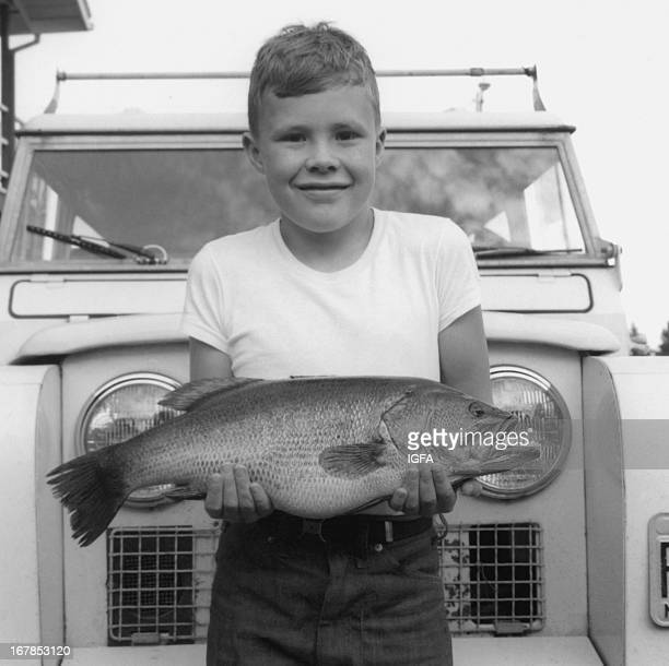 LAND 'O LAKES WISCONSIN SEPTEMBER 1969 A boy stands in front of a jeep holding a largemouth bass caught in Land 'O Lakes Wisconsin in September 1969
