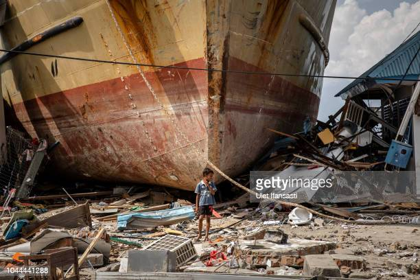 A boy stands in front of a stranded ship after a deadly tsunami struck the area on October 2 2018 in Donggala Central Sulawesi Indonesia Over 1200...