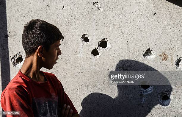 TOPSHOT A boy stands near impacts of projectile on a wall near the explosion scene following a late night attack on a wedding party that left at...