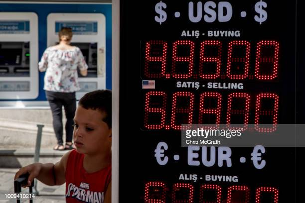 A boy stands next to a currency exchange sign on August 2 2018 in Istanbul Turkey The Turkish Lira dropped to a record low passing 5 TL to the dollar...