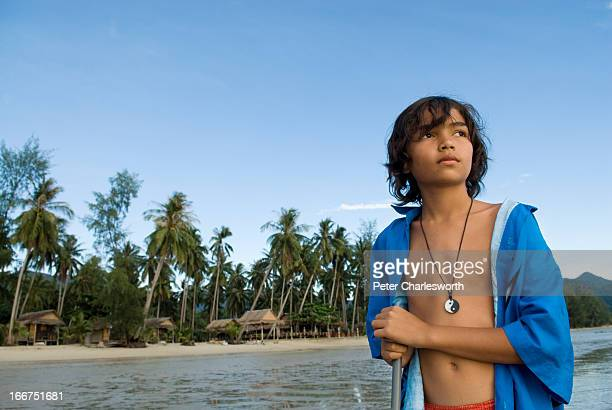 A boy stands on a beautiful tropical beach on the west coast of Koh Chang island MODEL RELEASED