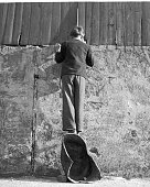 Boy stands on a coal scuttle to peer over the wall of a sports in picture id75358373?s=170x170