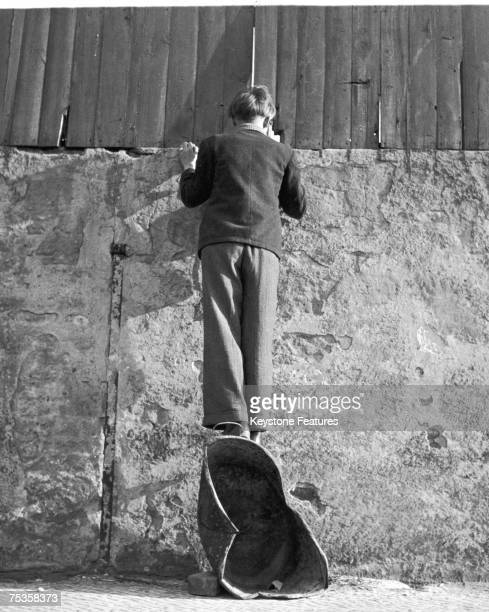 A boy stands on a coal scuttle to peer over the wall of a sports stadium in Berlin 8th January 1951
