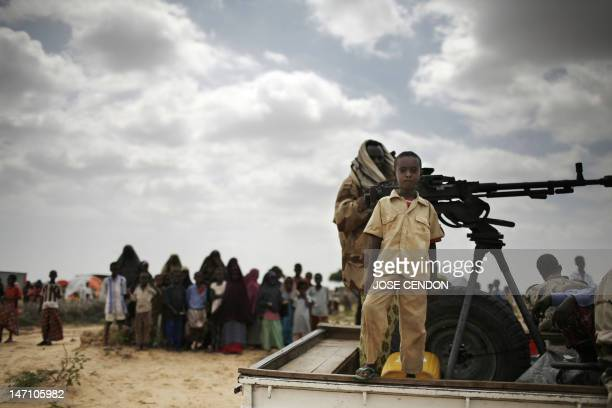 A boy stands on a vehicle with Somali soldiers in Daymarudi Camp 10 December on the outskirts of Mogadishu Backtoback bloody clan battles in Somalia...