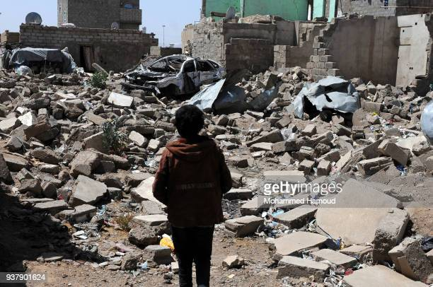 A boy stands on rubble of a house destroyed in 26 March 2015 in an airstrike carried out by the Saudiled coalition on March 24 2018 in Sana'a Yemen