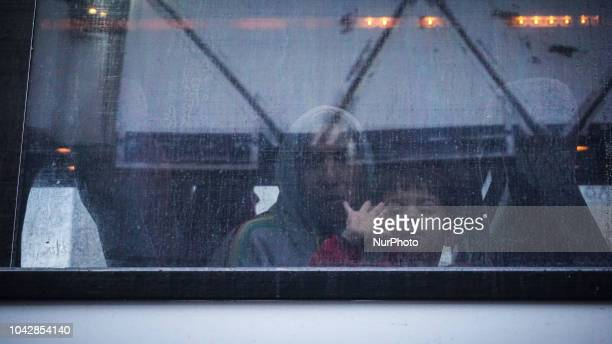 A boy stands on the window of the coach bus as salutes following boarding At the Port Piraeus 29 September 2018 Thousand migrants and refugees are...