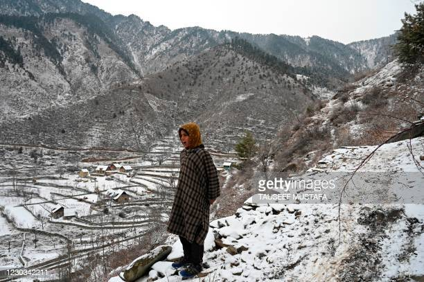 Boy stands on top of a mountain after snowfall on the outskirts of Srinagar on December 29, 2020.