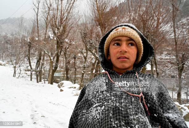 Boy stands over a mountain after snowfall on the outskirts of Srinagar on December 29, 2020.