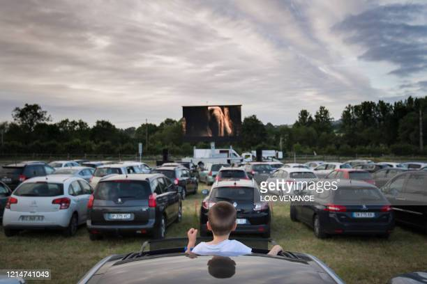 TOPSHOT A boy stands through the sunroof as cinemagoers watch a movie from their cars at a drivein theater in Les Herbiers western France on May 22...