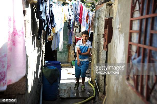 A boy stands under drying laundry hung across an alley way in the ElWiam shanty town in the Djasr Kasentina Wilaya in the capital Algiers on April 9...