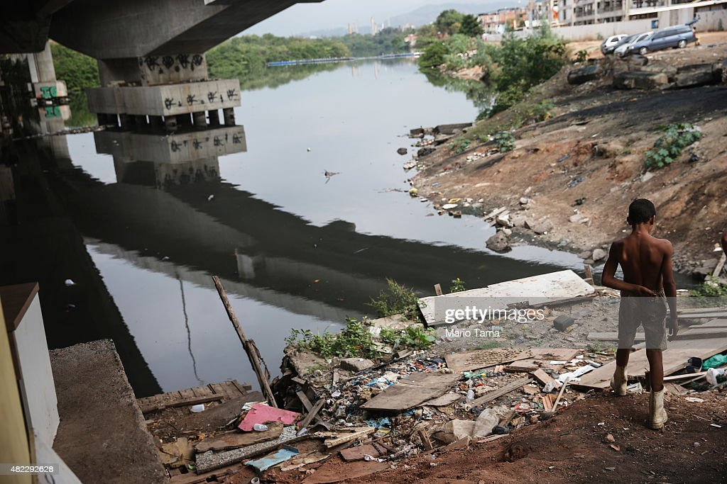A boy stands while looking for items to recycle along the polluted Cunha canal which flows into the notoriously polluted Guanabara Bay, site of sailing events for the Rio 2016 Olympic Games, on July 29, 2015 in Rio de Janeiro, Brazil. The Rio government promised to clean 80 percent of pollution and waste from the bay in time for the games but admits that goal now is unlikely to be reached. August 5 marks the one-year mark to the start of the Rio 2016 Olympic Games.