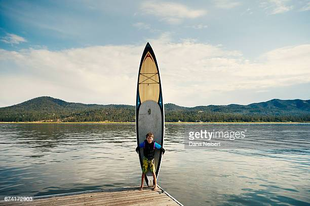 a boy stands with his paddle board on a dock. - big bear lake stock pictures, royalty-free photos & images