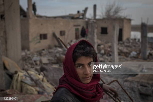 A boy stands works amid destroyed buildings on February 16 2019 in Hajin Syria Civilians have begun returning to some small towns close to Bagouz...