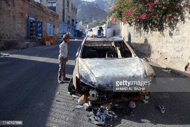 Boy stares at a car that was burned during recent heavy clashes between pro-government militias in Yemen's southern city of Taez on April 29, 2019.