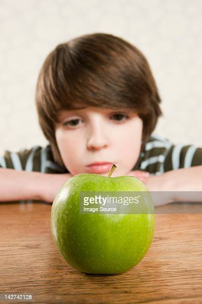 Boy staring at an apple