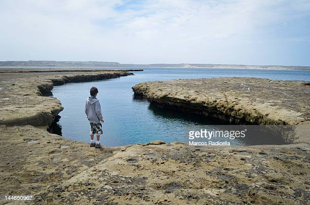 boy staring by sea on peninsula valdes - radicella stock photos and pictures