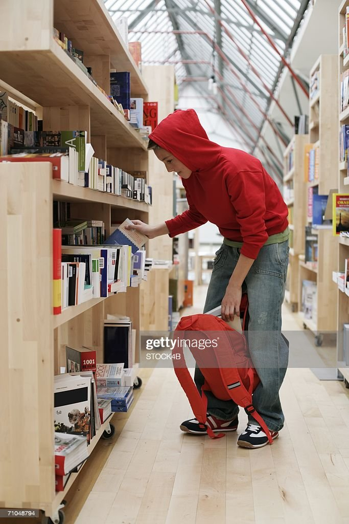Boy stealing a book in a library : Stock Photo