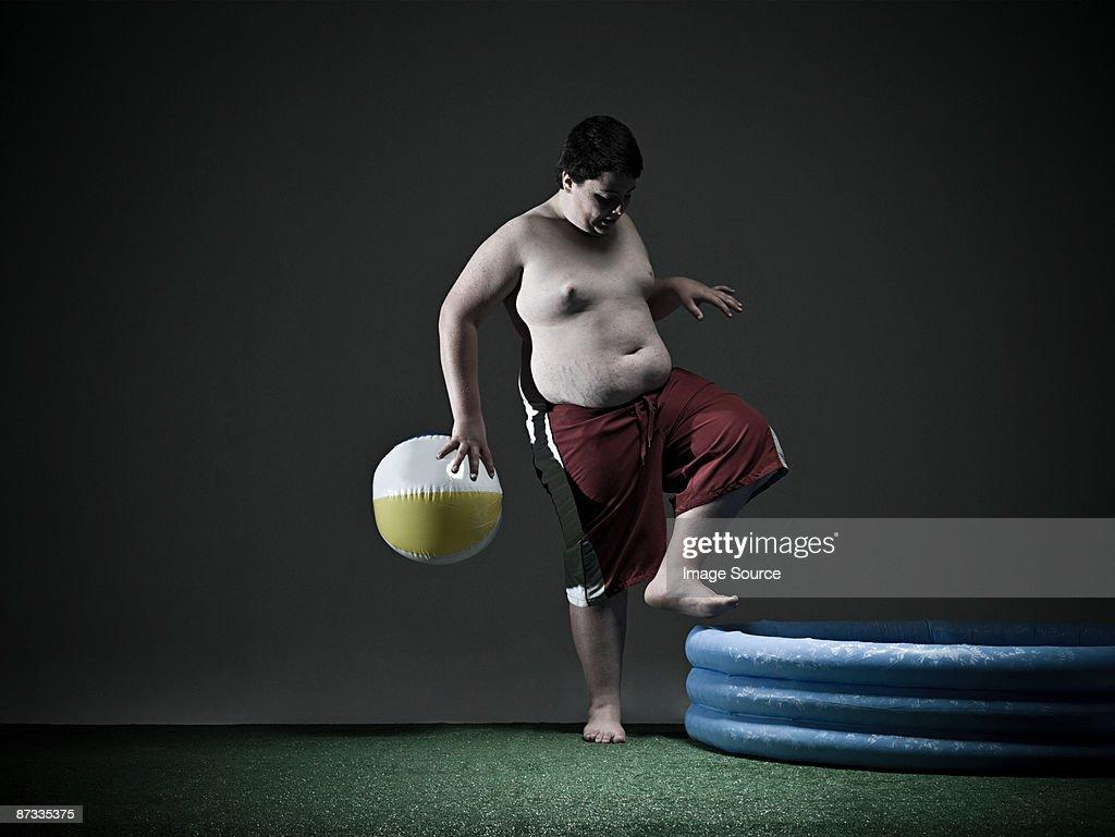 Boy stepping into paddling pool : Stock Photo