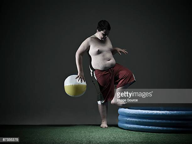 boy stepping into paddling pool - chubby boy stock photos and pictures