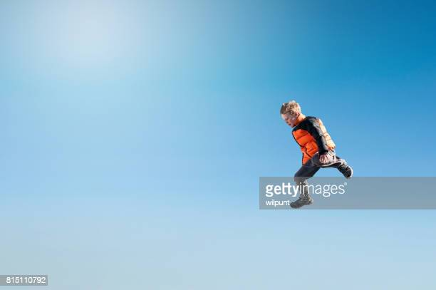 Boy stepping off Flying in blue sky