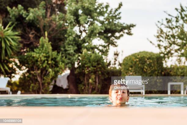Boy sticking his head out of a pool (outdoors)