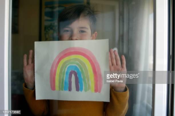 boy sticking his rainbow drawing on home window. coronavirus quarantine concept - esperar fotografías e imágenes de stock