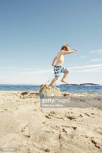 Boy insuperable en construir castillos de arena en la playa