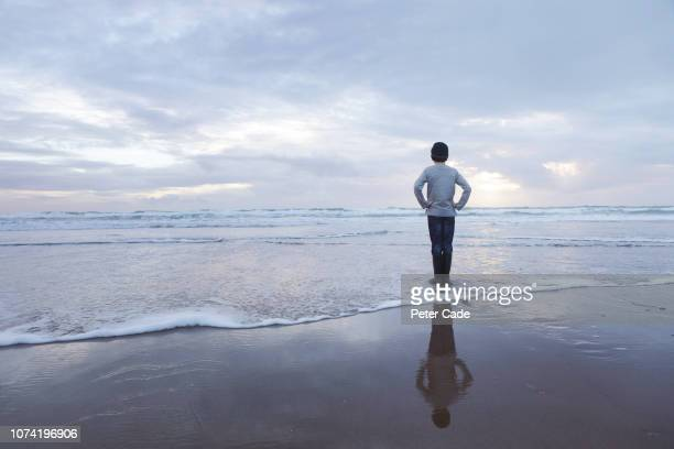 boy stood in water looking out to sea in winter - tide stock pictures, royalty-free photos & images