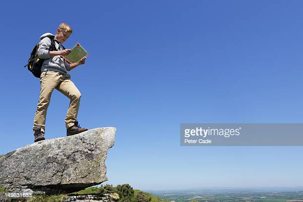 boy stood on rock looking at map