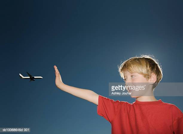 Boy (6-7) stopping airplane against sky