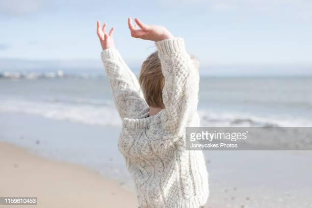 boy stretching arms on beach - verdecktes gesicht stock-fotos und bilder