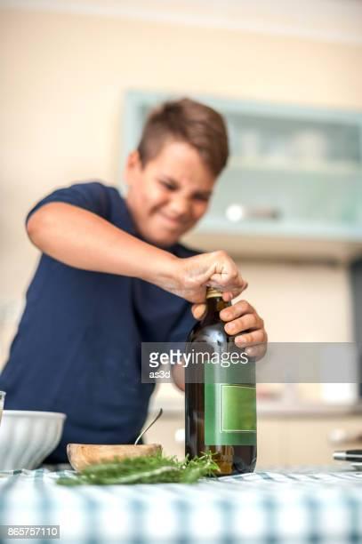 rapaz, lutando para tirar a tampa da garrafa - esforço - fotografias e filmes do acervo