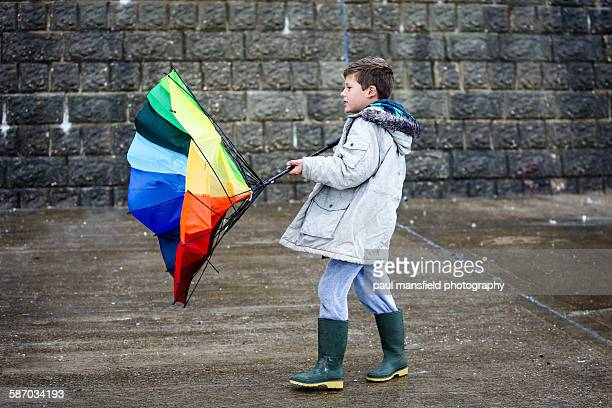 Boy struggling with broken umbrella