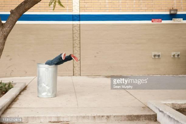 Boy stuck in dustbin upside down