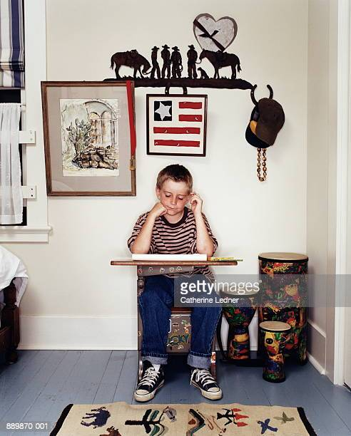 Boy (6-8) studying at desk in bedroom