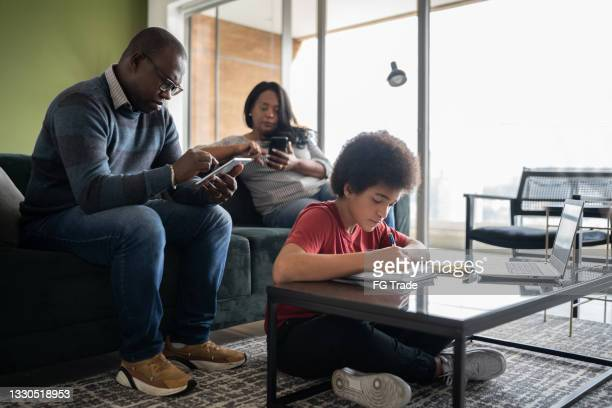 boy studying at home and parents using portable information devices in the living room - portable information device imagens e fotografias de stock
